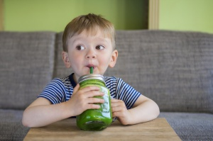 Cute little boy drinking a green smoothe