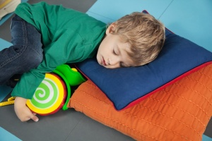 Cute boy sleeping with toy in kindergarten